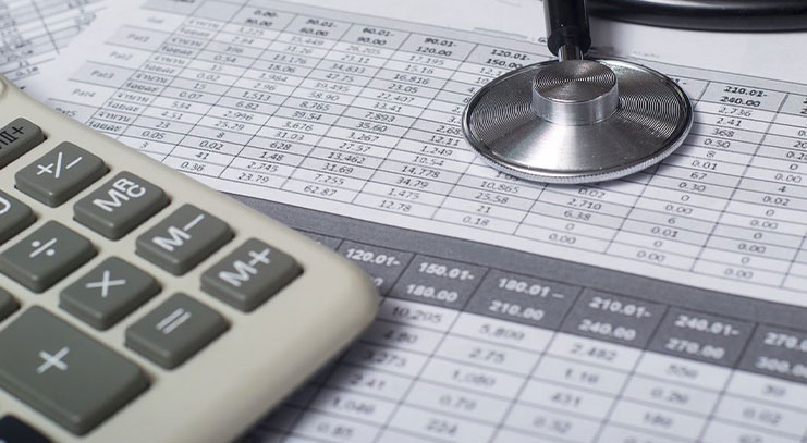 Calculator next to stethoscope on number grid paper